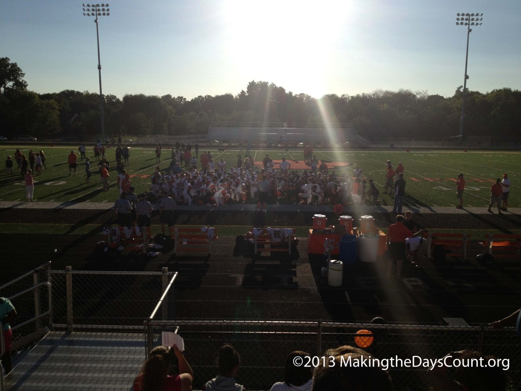 the varsity and the sophomore squads meet at the 50 yard-line at Red Grange field